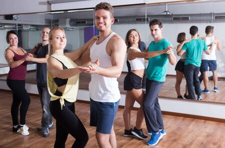 Group of positive adults dancing salsa together in dance class