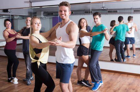Groupe d'adultes positifs dansant la salsa ensemble en cours de danse
