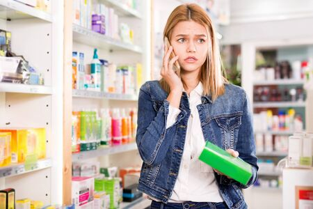 Upset pleasant  girl talking on the phone and choosing drugs at the pharmacy