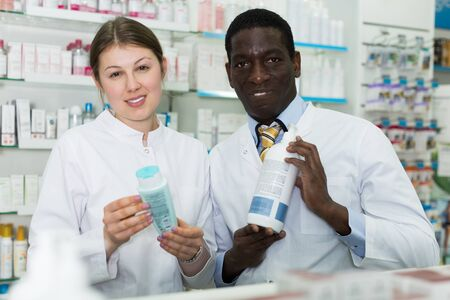 Portrait two experienced pharmacists standing in interior of modern pharmacy