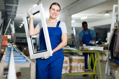 Portrait of woman worker who is standing with window frame in the pvc workshop. Archivio Fotografico