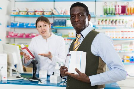 Confident African American male pharmacist working in pharmacy, proposing medicines