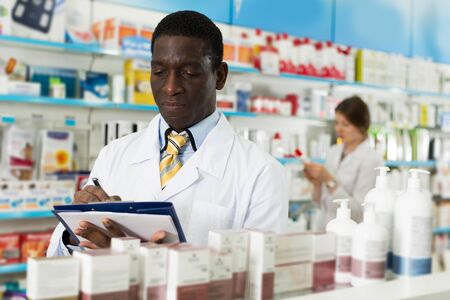 Confident African American male pharmacist taking inventory of medicines in pharmacy