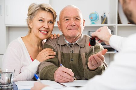 Husband and wife preparing new car papers in bank