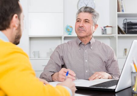 Man and mature bank employee discuss and sign credit agreement in office Фото со стока