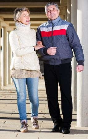 Smiling senior couple walking along corridor fenced with columns