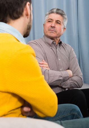 Adult father and young son discuss and solve family problems