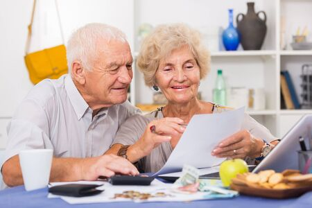Positive mature couple with papers and laptop at home