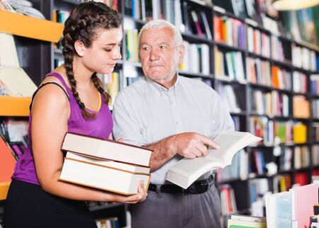 elderly man and granddaughter discuss a book in a bookstore