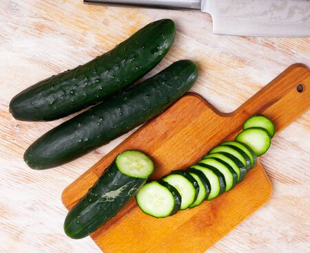 Chopped organic cucumbers on wooden background. Healthy nutrition concept