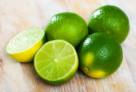 Closeup of fresh limes with chopped slices on wooden background. Vitamin cooking ingredients