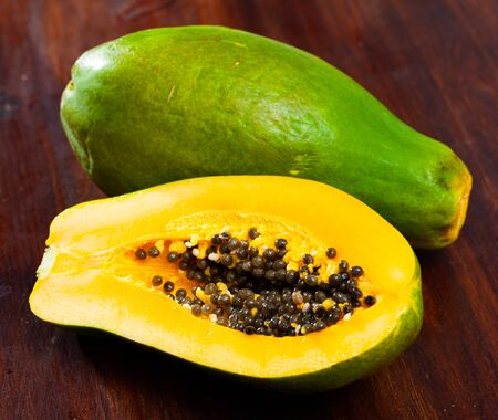 Closeup of whole and halved fresh ripe papaya on wooden surface. Tropical fruit
