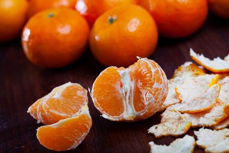 Closeup of peeled and whole clementines on dark wooden background Stock Photo