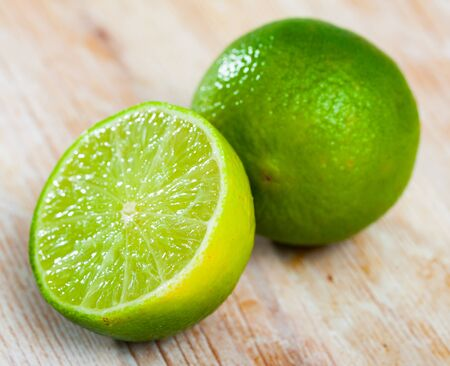 Whole and sliced ripe organic green limes on wooden table
