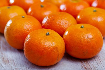 Whole fresh juicy clementines on pile on wooden table. Vitamin cooking ingredients
