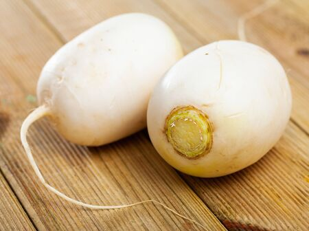 Fresh white turnips on wooden table. Vegetarian food concept