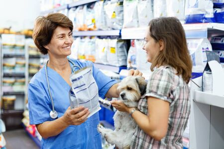Elderly glad cheerful smiling female veterinarian recommending pet food to young woman visiting pet store with her puppy