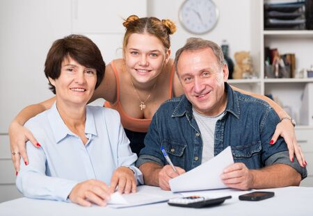Smiling parents are reading utility bill with their adult daughter at home.
