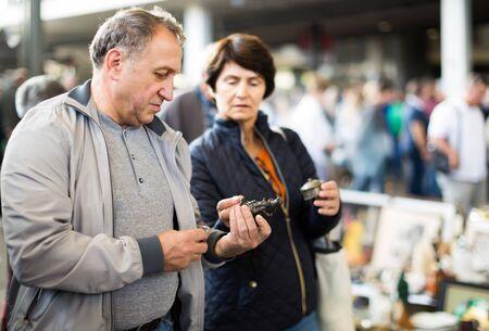 Happy mature spouses buying retro handicrafts on indoor flea market Reklamní fotografie