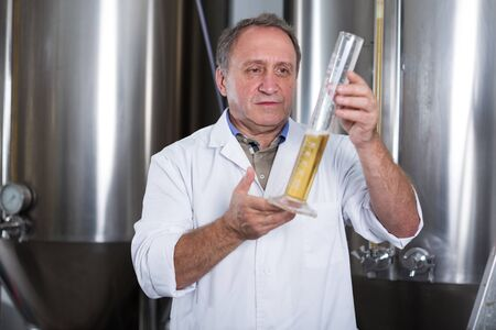 Man expert is analizying the quality of beer in flask in laboratory. Фото со стока