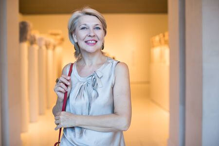 Positive mature woman standing in hall at the art museum Фото со стока