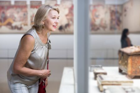 Mature woman standing near the ancient exhibit in art museum Фото со стока