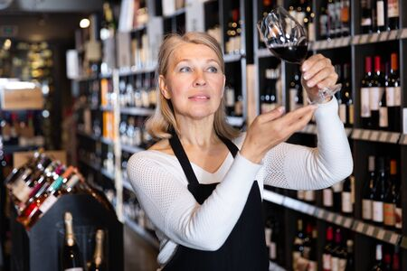 Confident mature female winemaker holding glass of wine, checking it in wine store Foto de archivo