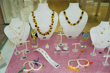 Variety of necklaces, bracelets and earrings from semiprecious stones offered for sale in showcase of shop