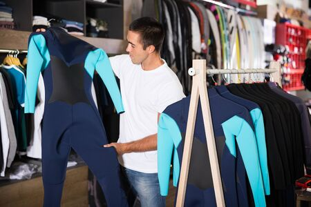 Young male chooses sportswear in a clothes store Фото со стока