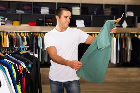 Male consumer choosing colorful t-shirt in the boutique