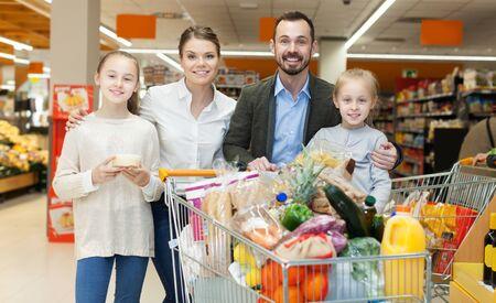 Une famille heureuse de quatre personnes se tient debout avec des achats au supermarché Banque d'images