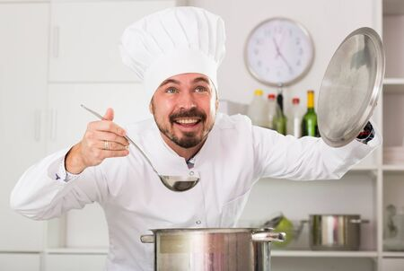 Smiling male cook checking taste of food while preparing in kitchen