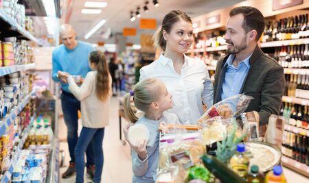 Une famille positive et joyeuse regarde sur des étagères avec des produits au supermarché. Banque d'images