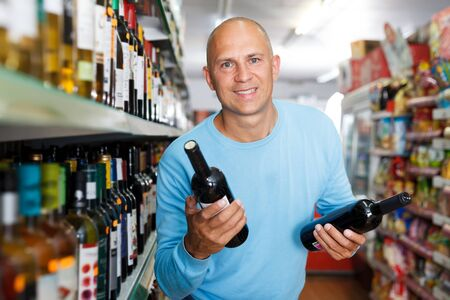 Portrait of concentrated man  buying  wine in stor