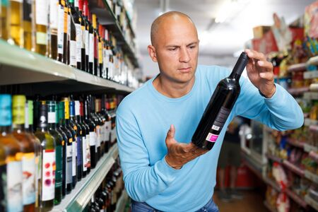 Portrait of concentrated man choose what variety of  wine to buy in supermarket