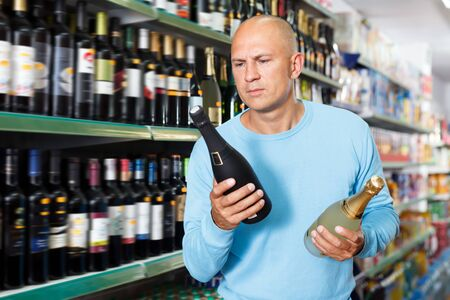 Portrait of ordinary male customer selecting wine in supermarket