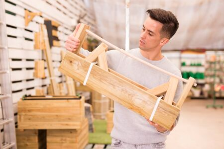 Young man choosing peculiar wooden planter for flowers at garden market