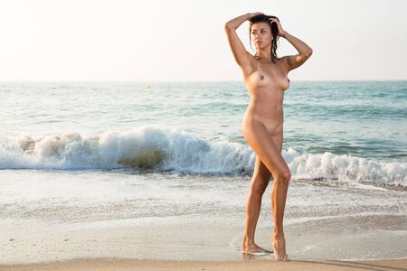 Sexy naked young woman standing  and enjoying on the sandy beach