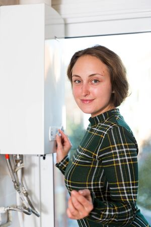 Smiling woman adjusting gas water heater at home