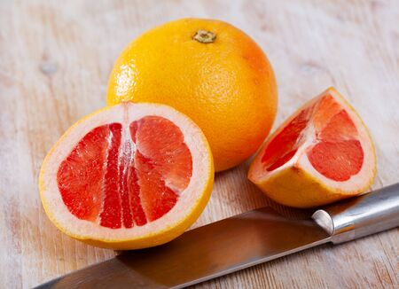 Sliced fresh juicy pink pomelo on wooden table. Concept of health benefits of citrus fruits