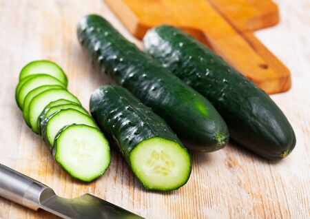 Closeup of fresh cucumbers with chopped slices on wooden surface. Vegetarian food concept