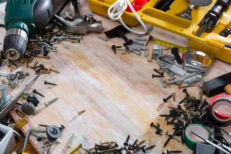 Various screws, bolts, tools on a wooden table. Space for text