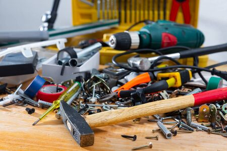 Various fasteners, supplies and hand tools in mess on wooden table. DIY home improvement concept