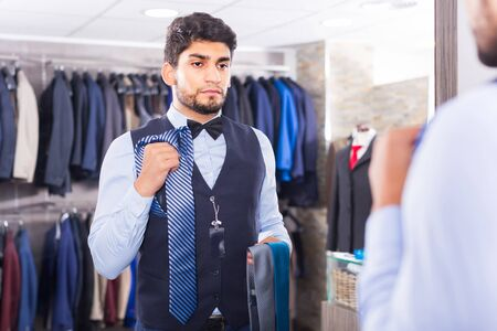 Customer male is picking up tie for waistcoat in front of the mirror in men's shop.
