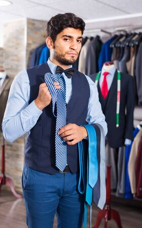 Person is picking up tie for waistcoat in men's shop.
