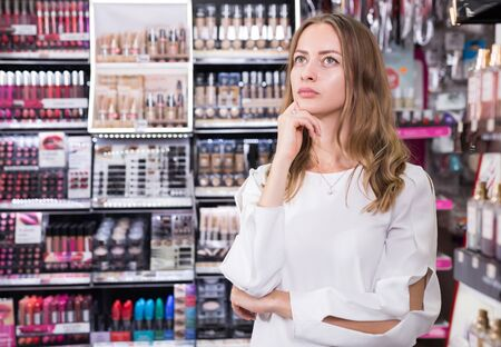 Portrait of puzzled girl having doubts in makeup store