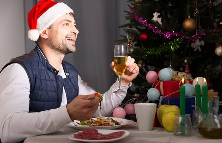 Young man in hat celebrating New Year, having dinner with champagne and watching tv