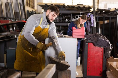 Craftman rules the part with a hammer on the anvil