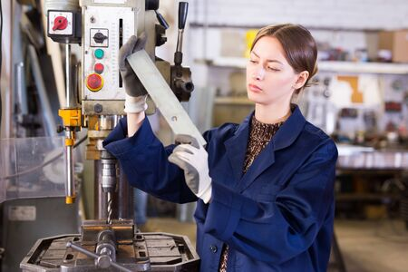 Skilled young craftswoman working on metal structures drilling machine in industrial workshop