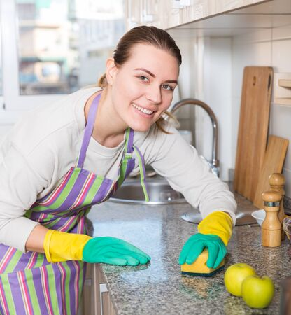 Young housewife in gloves is cleaning kitchen with detergent at the home. Stock Photo